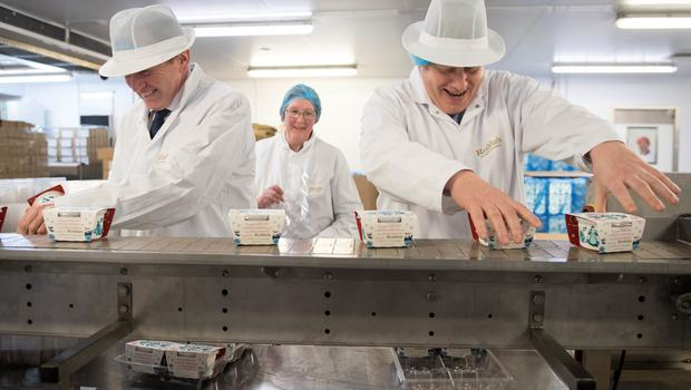 Boris Johnson, right, and Tory environment minister George Eustice helping on the production line (Stefan Rousseau/PA)