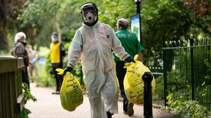 A city council worker carries rubbish from a coronavirus testing centre at Spinney Hill Park in Leicester (PA)