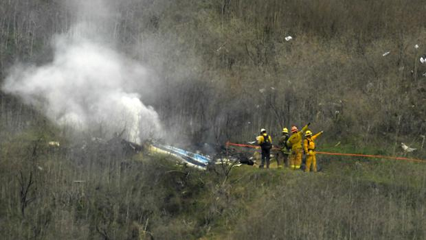 Firefighters work the scene of a helicopter crash where former NBA star Kobe Bryant died (Mark J Terrill/AP)