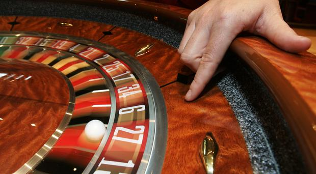 File photo dated 5/2/2008 of a croupier with a roulette table.