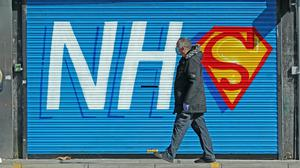 A person walks past a mural supporting the NHS in Kensington, Liverpool (Peter Byrne/PA Wire)