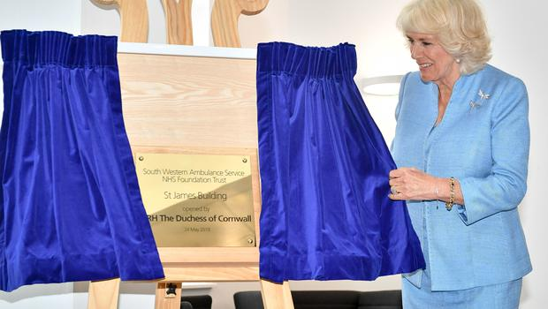 The Duchess of Cornwall (left) unveils a plaque during an official visit to open the South Western Ambulance Service (SWASFT) 999 Control Hub in Bradley Stoke (Ben Birchall/PA)