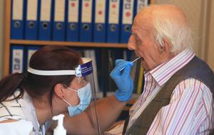Assistant manager Claire Welford administers a coronavirus swab test on resident Harry Hall, 94 (Owen Humphreys/PA)