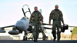 Squadron leaders Ian Dornan, left, and Stephen Beardmore walk away from their jet after the final Tornado flight over RAF Marham in Norfolk (Joe Giddens/PA)