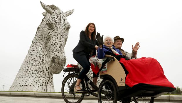 Public Health Minister Aileen Campbell pedals with Mary Duncan, 90, and Jim Taylor, 96, at the Kelpies in Falkirk, as the Cycling Without Age scheme is rolled out across Scotland (Andrew Milligan/PA)