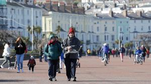People walk along the promenade in Llandudno, north Wales, as the Government continues to advise the public to reduce social interaction due to the coronavirus outbreak (Martin Rickett/PA)