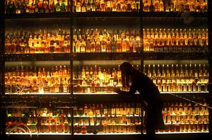 A member of staff looking at the Diageo Claive Vidiz Scotch whisky collection (David Cheskin/PA)