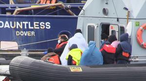 A group of people, thought to be migrants, waiting on a Border Force rib to come ashore at Dover marina in Kent, after a small boat incident in the English Channel.