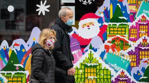 People wearing face masks pass a Christmas window display on Oxford Street, London (PA)