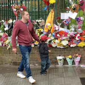 People leave flowers at the scene at the junction of Artillery Place and John Wilson Street which has become a shrine to Drummer Lee Rigby