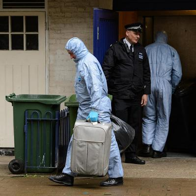 Police forensics officers remove evidence from a flat at Macey House in Greenwich, south-east London
