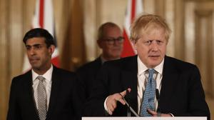 Chancellor Rishi Sunak with Prime Minister Boris Johnson arrive for a media briefing in Downing Street (Matt Dunham/PA)