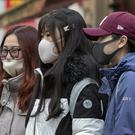 Members of the Chinese community in Manchester wearing face masks (PA)