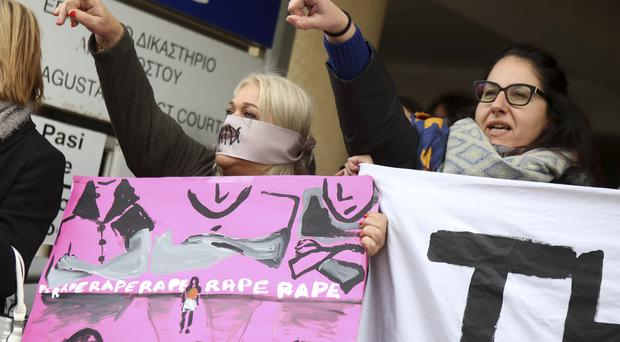 Women protest outside Famagusta District Court in Cyprus in support of a British woman who has been found guilty of lying about being gang-raped in Cyprus (Philippos Christou/AP)