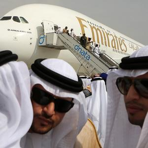 Emirati officials greet each other in front of an Emirates Airbus A380 on display during the opening day of the Dubai Airshow (AP)