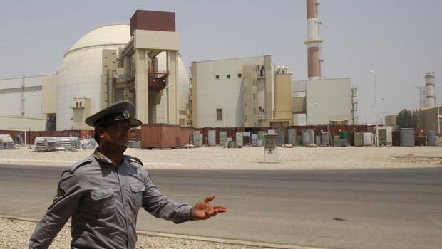 An Iranian security official directs media at the Bushehr nuclear power plant, with the reactor building seen in the background, just outside the southern city of Bushehr, Iran (Vahid Salemi/AP)