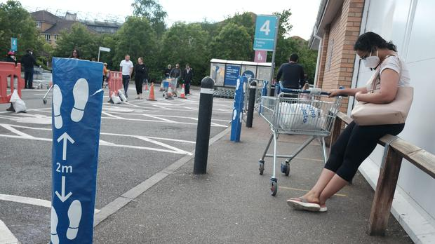 People practice social distancing while queuing outside a Tesco Extra store in Twickenham (Yui Mok/PA)