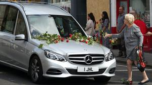People place flowers on the funeral cortege of Xander Irvine, the three-year-old boy killed in an accident in Morningside, Edinburgh (Jane Barlow/PA)