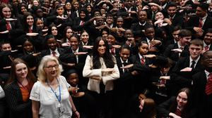 Meghan makes the the 'equality' sign following a school assembly (Ben Stansall/PA Wire)