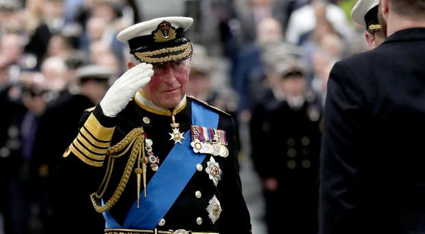 The Prince of Wales salutes during the commissioning ceremony of the Royal Navy aircraft carrier, HMS Prince of Wales (Steve Parsons/PA)
