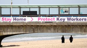 People make their way along a deserted beach front in Bournemouth, Dorset (Andrew Matthews/PA)