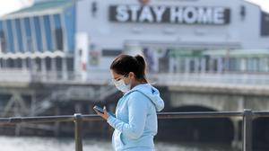 A woman wearing a mask looks at her phone (Andrew Matthews/PA)