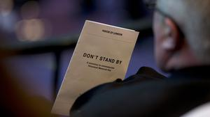 A guest holding a programme with the title Don't Stand By during a Holocaust Memorial Day ceremony, in The Chamber, City Hall, London