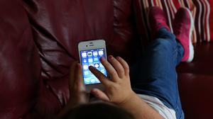 A child using an Apple iPhone smartphone (Peter Byrne/PA)