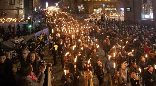 Members of the public take part in the annual torchlight procession (Jane Barlow/PA)