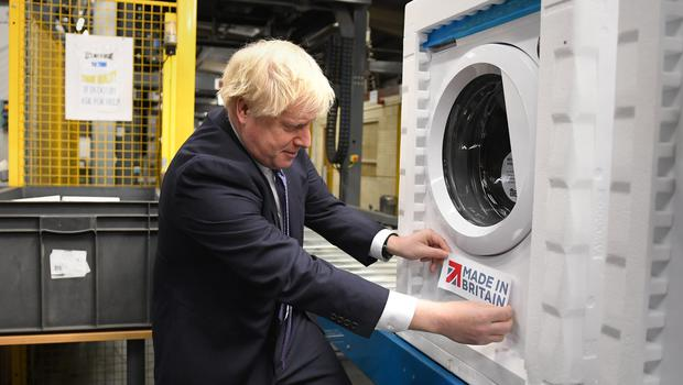Boris Johnson puts a Made In Britain sticker on a washing machine during a visit to Newton Aycliffe (Stefan Rousseau/PA)