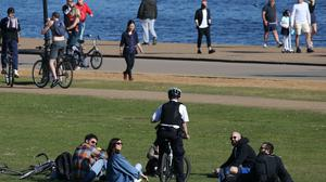 A police officer speaks to a group relaxing in Hyde Park as the sun brings crowds to public places (Jonathan Brady/PA)
