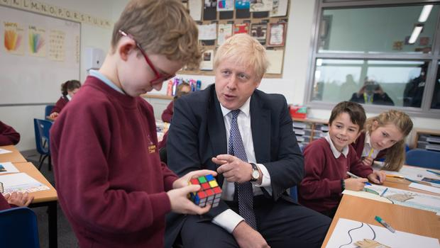 The PM watches a pupil complete a Rubik's Cube (Stefan Rousseau/PA)