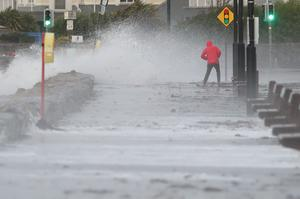 A man avoids the waves at Salthill promenade, Co Galway, during Storm Callum (Brian Lawless/PA)