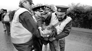 Ambulance workers help an injured picket after a confrontation with police outside the Orgreave coking plant during the miners' dispute
