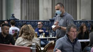 A waiter takes orders on the street at Di Maggio's outdoor restaurant area in Glasgow city centre (Jane Barlow/PA)