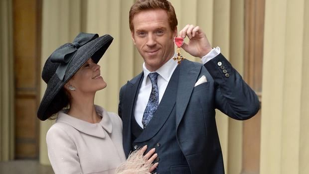 Actor Damian Lewis with his wife Helen McCrory as he holds his Officer of the Order of the British Empire (OBE) after the investiture ceremony at Buckingham Palace