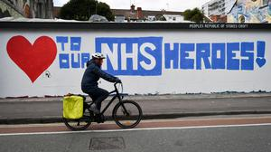 A cyclist passes street art in Stokes Croft, Bristol, which pays tribute to the NHS (Ben Birchall/PA)
