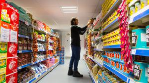 File photo of a member of staff stacking shelves at the Community Supermarket, in west Norwood, south London (Dominic Lipinski/PA).