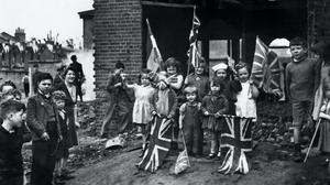 Young residents celebrate VE Day amid the ruins of their home in Battersea (PA)