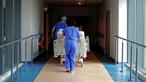 Medical staff transfer a patient through a corridor at The Royal Blackburn Teaching Hospital in East Lancashire during the outbreak of the coronavirus disease (Hannah McKay/PA)