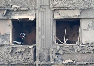A firefighter searches through the rubble