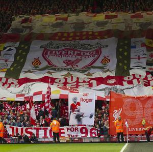 Liverpool supporters hold banners prior to a minute's silence at their match on Sunday