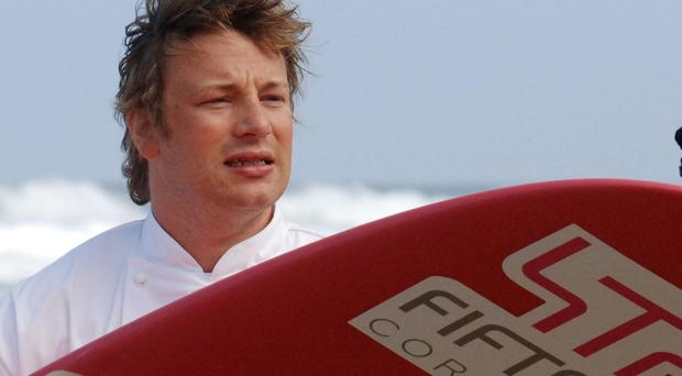 Jamie Oliver with his surf board at the beach (Barry Batchelor/PA)