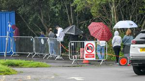 People queue to access the coronavirus testing centre at Caerphilly Leisure Centre (Ben Birchall/PA)