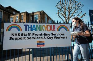 A woman wearing a face mask walking past a 'Thank You' to NHS staff and key workers banner on the Isle of Dogs, east London. (Yui Mok/PA)