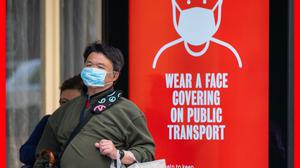 A man wearing a protective face mask waits at a bus stop in central London displaying a notice advising passengers to wear a face covering on public transport (Dominic Lipinski/PA)