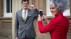 Judy Murray photographs her son Jamie Murray after he received his OBE