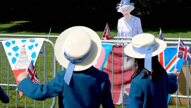 The real deal? Two schoolgirls wave at a cut-out of the Queen in Windsor (Owen Humphreys/PA)