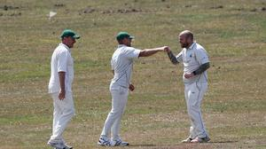Players fist bump as they celebrate a wicket in the match between Lyndhurst and Ashurst CC cricket club and Sway cricket club at Boltons Bench, near Lyndhurst. (Andrew Matthews/PA)