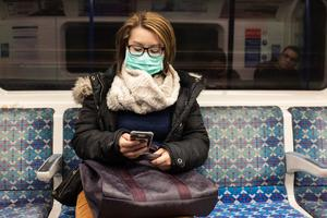 A woman in a face mask rides the Tube (Ian Hinchcliffe/PA)